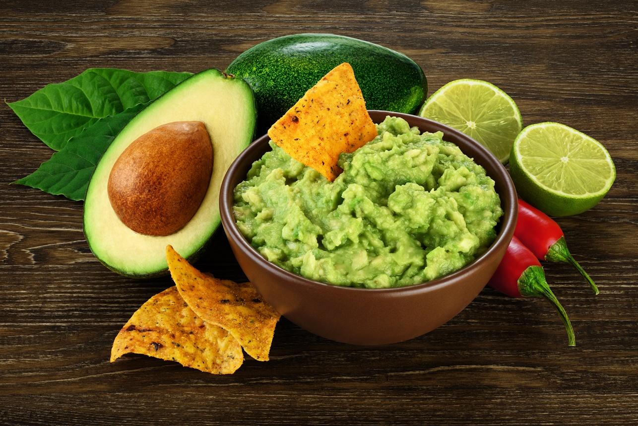 Guacamole servit cu tortilla chips într-un bol maro, alături de lime, ardei iute și avocado
