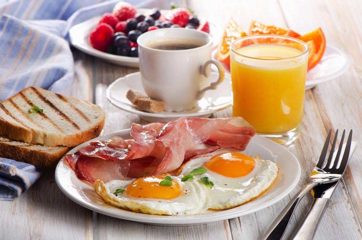 Pe masă este o farfurie cu două ouă ochiuri, cu niște felii de bacon. Alături se află o cafea și un suc de portocale și câteva fructe: zmeură, portocale și afine