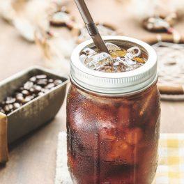 o masă de lemn pe care se află un borcan cu un pai de metal, boabe de cafea și este umplut cu Cold Brew
