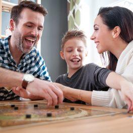 O familie fericită, mamă, fiu și tată, în timp ce se joacă împreună una din cele 5 activități creative de 1 iunie, într-un joc antrenant de societate