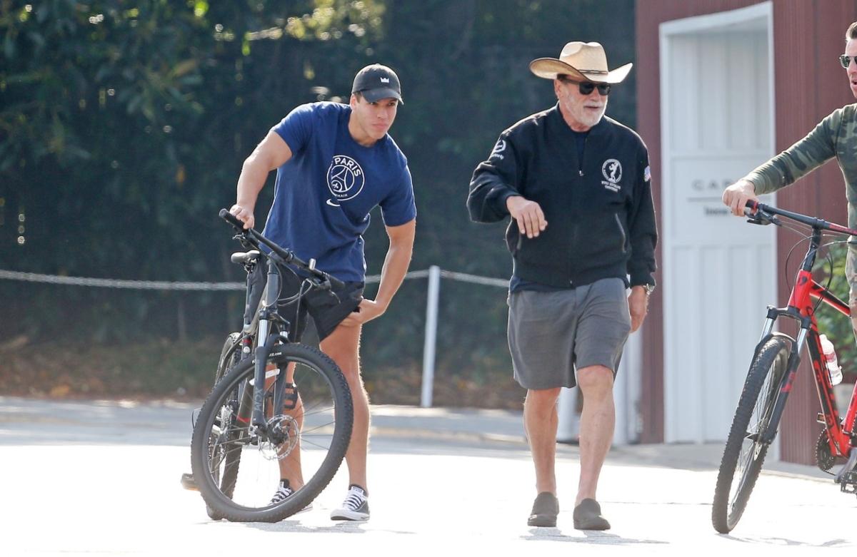 Arnold Schwarzenegger și Joseph Baena sunt îmbrăcați sport și se plimbă cu bicicletele