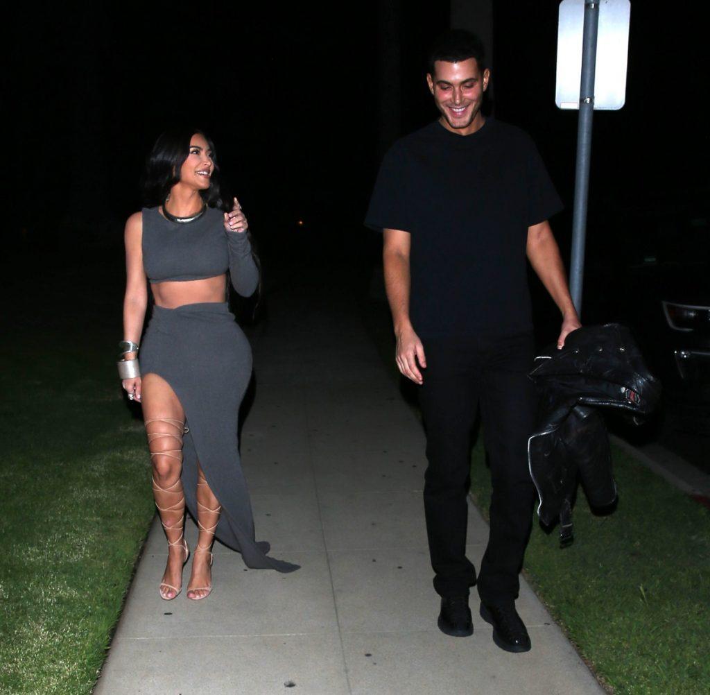 Kim Kardashian, în timp ce discută cu Jamie Reuben și merg împreună la petrecerea organizată de ziua lui