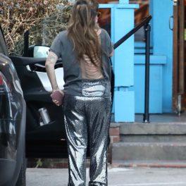 Lady Gaga, cu spatele către fotografi, într-un tricou cu spatele gol