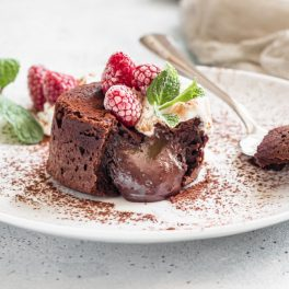 Lava cake cu ciocolată, așezată pe o farfurie albă, pudrată cu cacao și decorată cu zmeură și mentă.