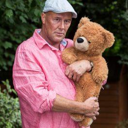 Mark Evans, într-o imagine în care ține un urs de pluș în brațe, îmbrăcat cu o cămașă roz, pantaloni deschiși la culoare și șapcă