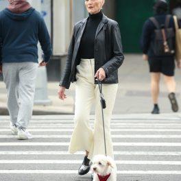 Maye Musk, îmbrăcată în haină de piele neagră, cu pantaloni eleganți, la plimbare cu cățelul, în New York