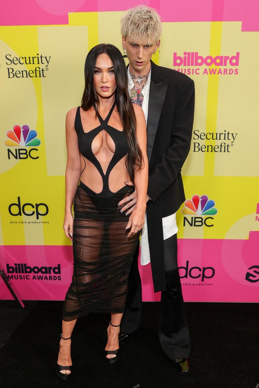 Megan Fox și Machine Gun Kelly, în timp ce stau îmbrățișați, pe covorul roșu la Premiile Billboard 2021