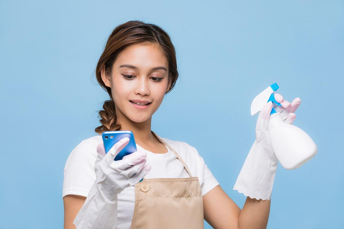 Femeie cu părul prins într-o coadă cu mănuși de curățenie care ține în timp ce studiază câteva metode de curățenie de pe internet