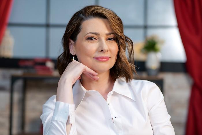 Mihaela Călin, cu mâna la obraz, în timp ce pozează pentru CaTine.ro