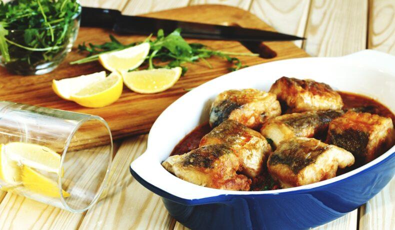 Pește cod în sos de roșii cu usturoi, într-un vas albastru, alături de felii de lămâie și rucola, pe un tocător de lemn