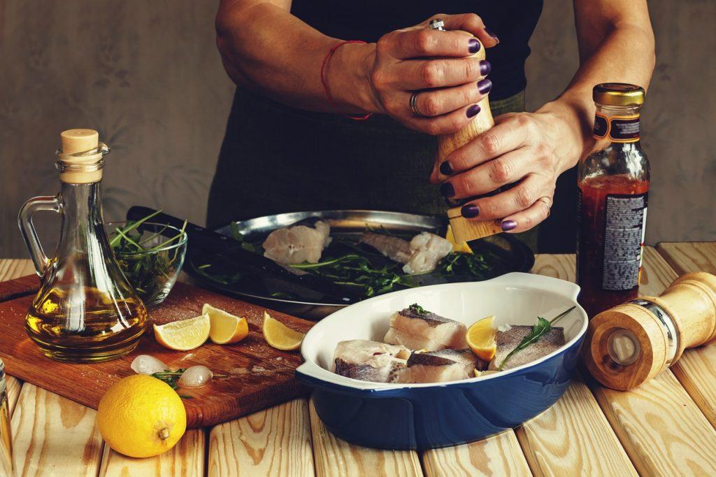 Bucăți de pește cod într-o formă ceramică albastră, pregătit pentru cuptor