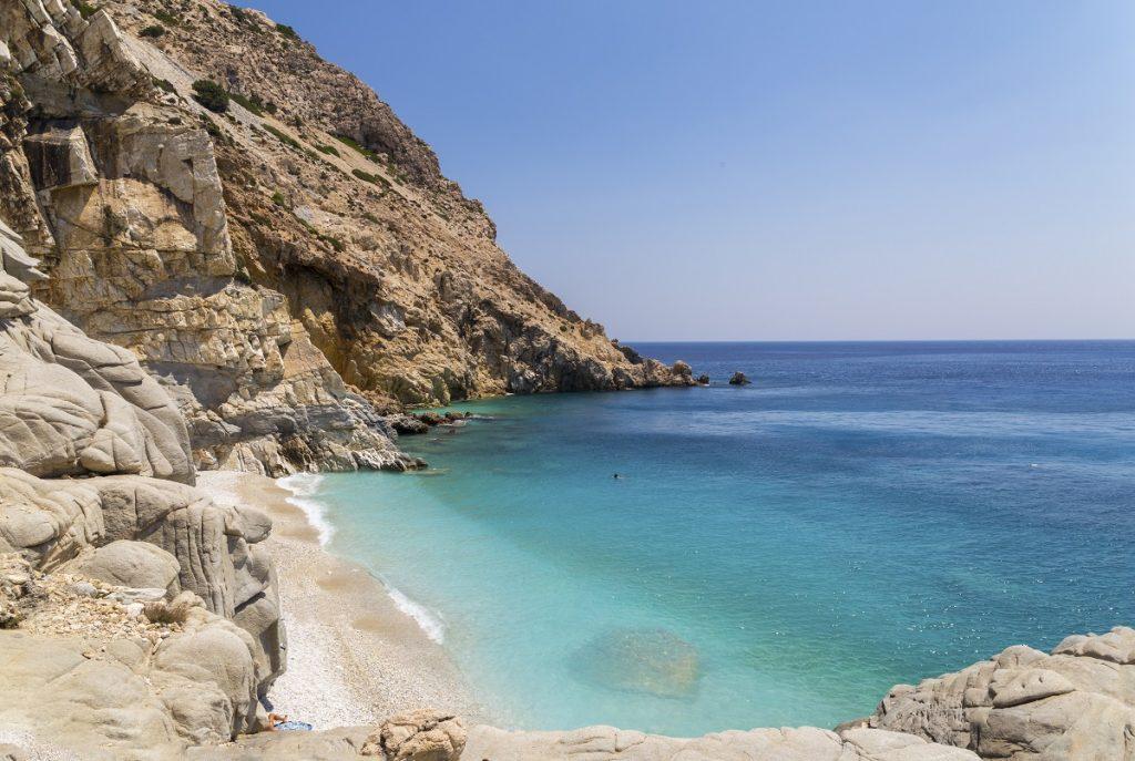 Peisaj care surprinde marea calmă, plaja și stâncile de pe insula Ikaria din Grecia
