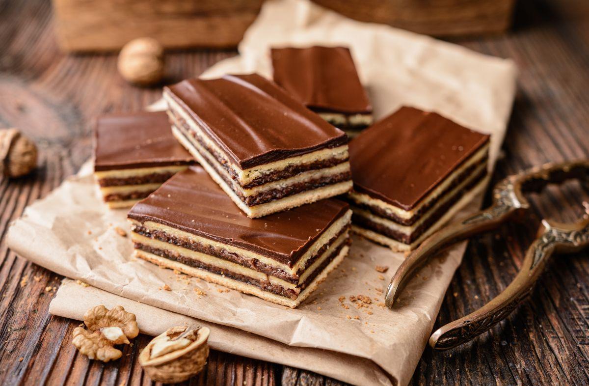 Prăjitură cu foi și cremă de cacao, tăiată bucăți și așezată pe o hârtie de copt împăturită.