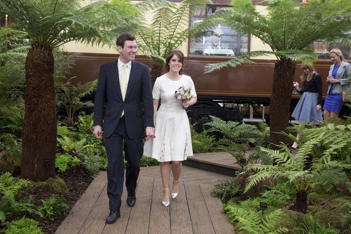 Prințesa Eugenie îmbrăcată într-o rochie albă în țimp ce ține în mână un buchet de flori, alături de Jack Brooksbank într-un portret pentru a celebra aniversarea soțului său