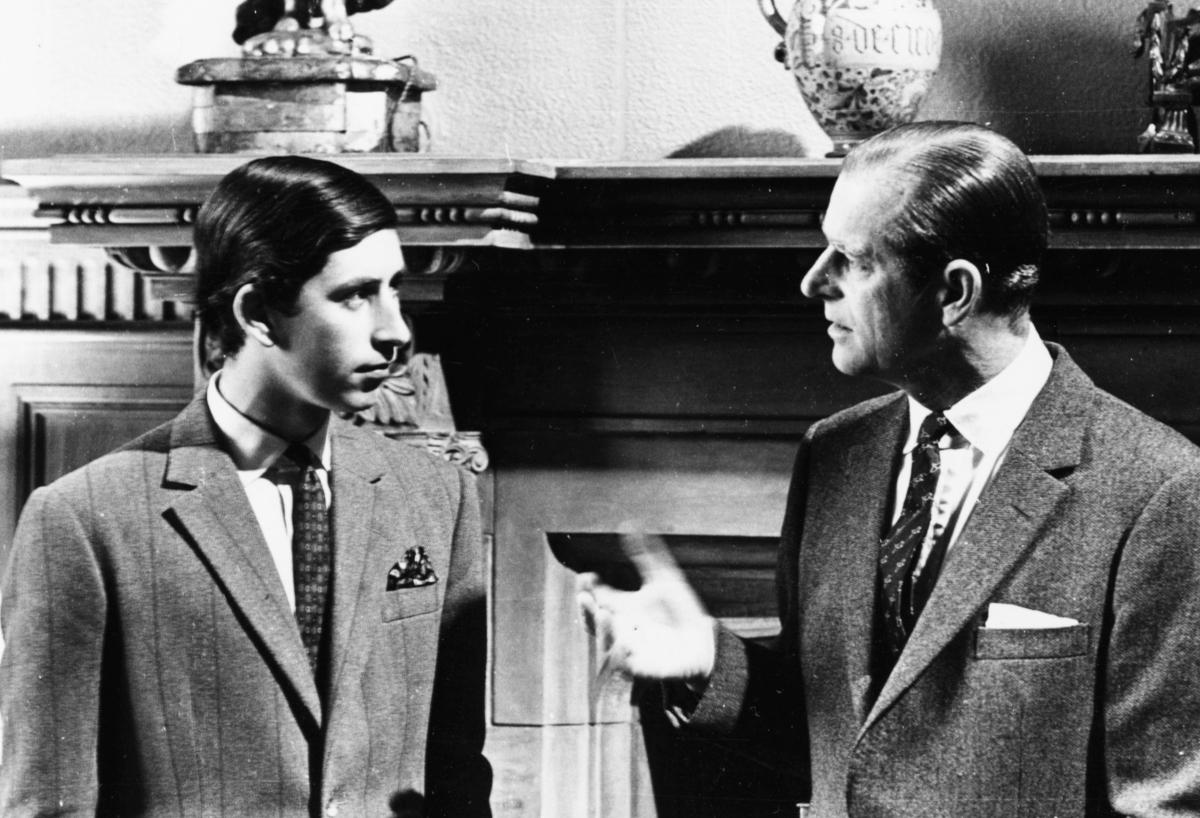 Prințul Charles alături de Ducele de Edinburgh într-o poză alb negru d când Charles era foarte tânăr. Cei doi sunt îmbrăcați la patru ace