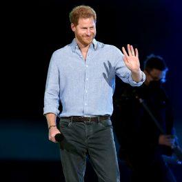 Prințul Harry, îmbrăcat lejer, în cămașă și pantaloni, pe scena concertului VAX Live