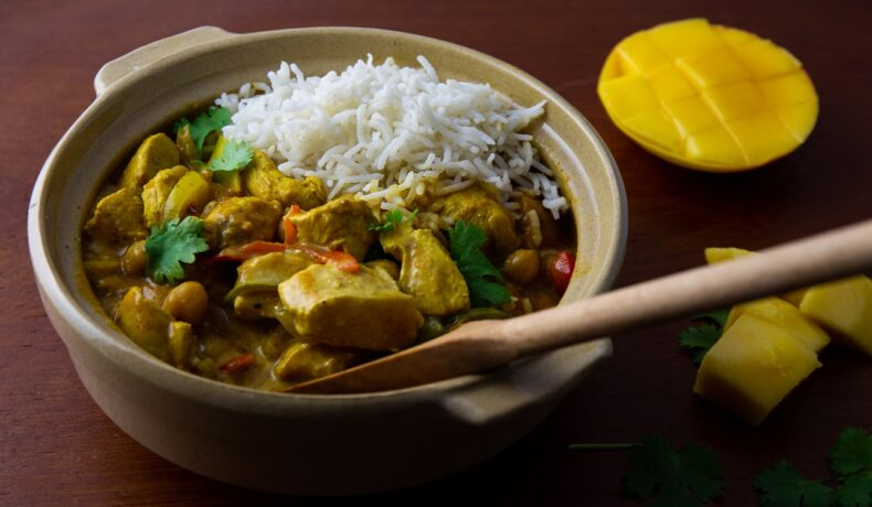 Pui cu mango și curry, alături de orez, într-un bol maro