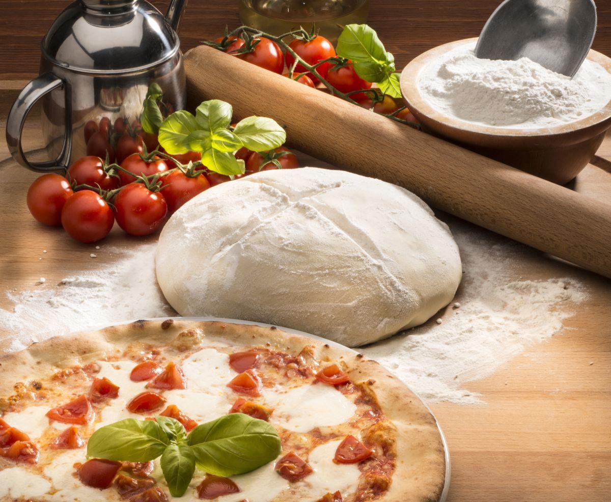 Aluat de pizza, așezat pe masă, alături de o pizza proaspăt scoasă din cuptor, roșii cherry, busuioc și făină.