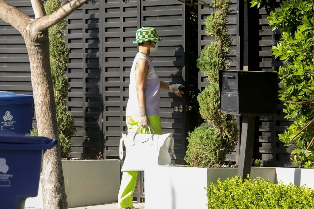 Rihanna, acoperită din cap până în picioare, cu pălărie pe cap, în haine în nuanțe de verde