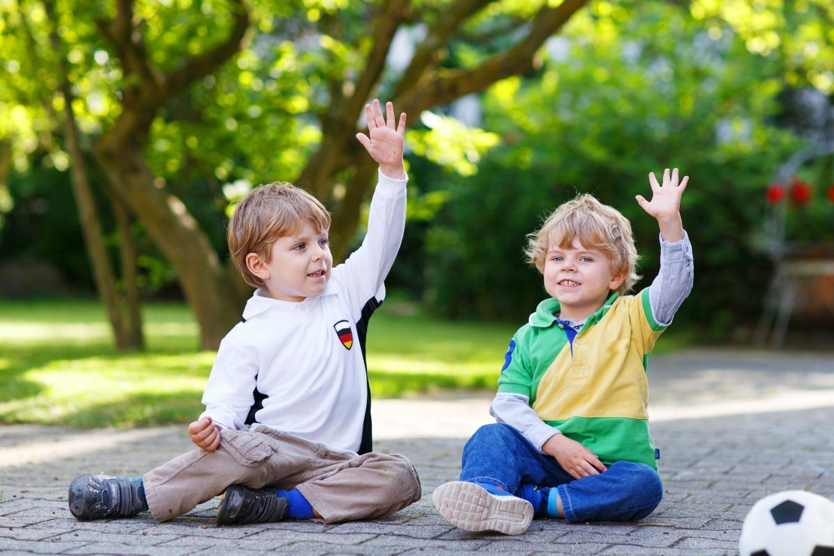 Doi copii stau așezați pe asfalt și țin câte o mână ridicată
