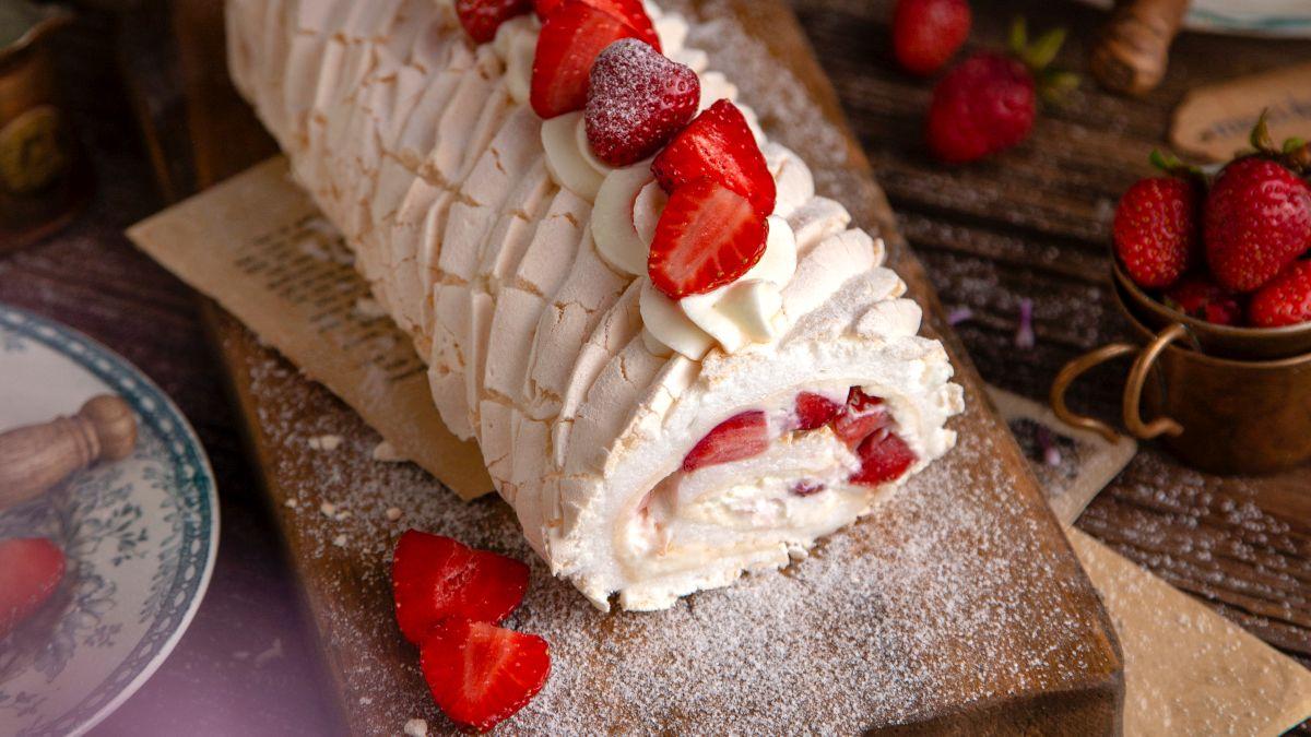 O ruladă de bezea cu cremă de vanilie și căpșuni, așezată pe un blat pudrat cu zahăr pubdră, alături de căpșuni.