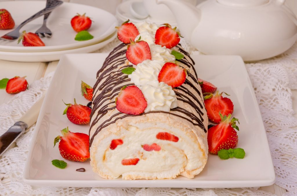 Ruladă de bezea pe un platou alb, decorată cu ciocolată și căpșuni