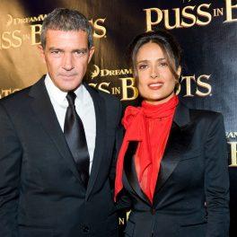 Salma Hayek alături de Antonio Banderas. Amândoi sunt îmbrăcați elegant. În spate au panoul cu numele producției Puss in Boots.