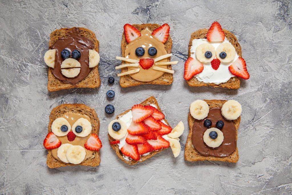 o masă cu șase sandwich-uri pentru copii decorate cu fructe precum afine, banane și căpșune pentru a crea imagini cât mai amuzante pentru cei mici