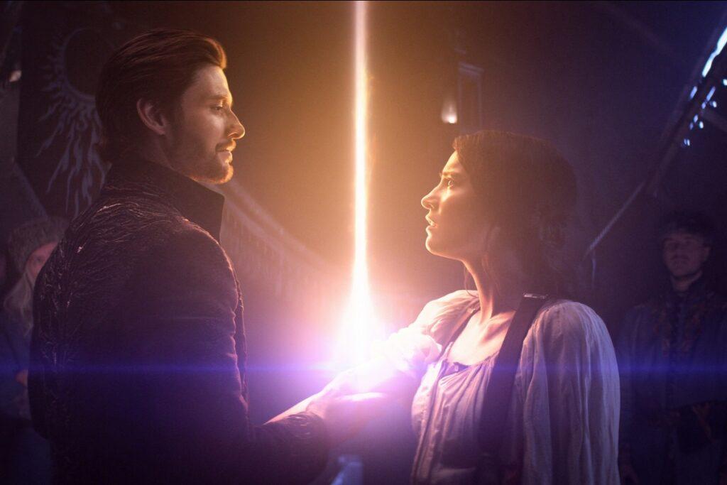 Un bărbat care ține în mână o sabie a luminii alături de o femeie care îl privește în ochi într-o scenă dintr-un seriale fantasy intitulat Shadow and Bone