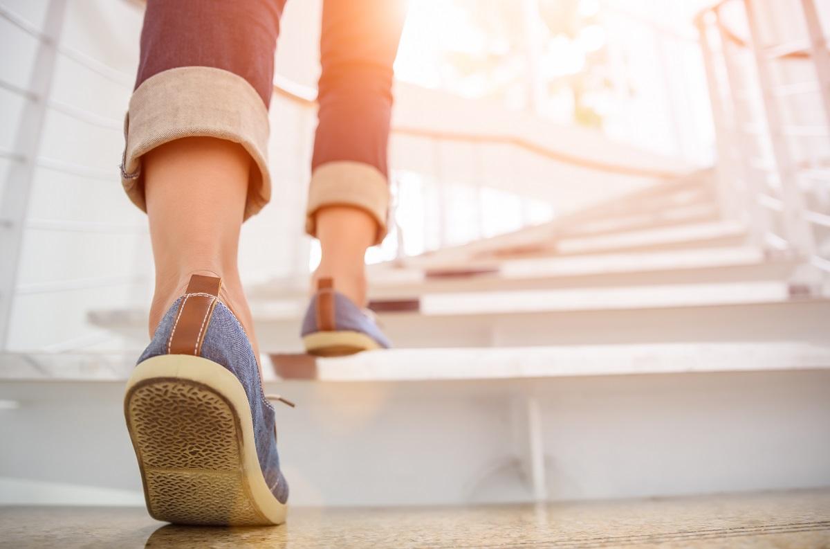 femeie care poartă blugi și teniși de culoare albastră în timp ce urcă scările albe pentru a arăta cum slăbești rapid și sănătos
