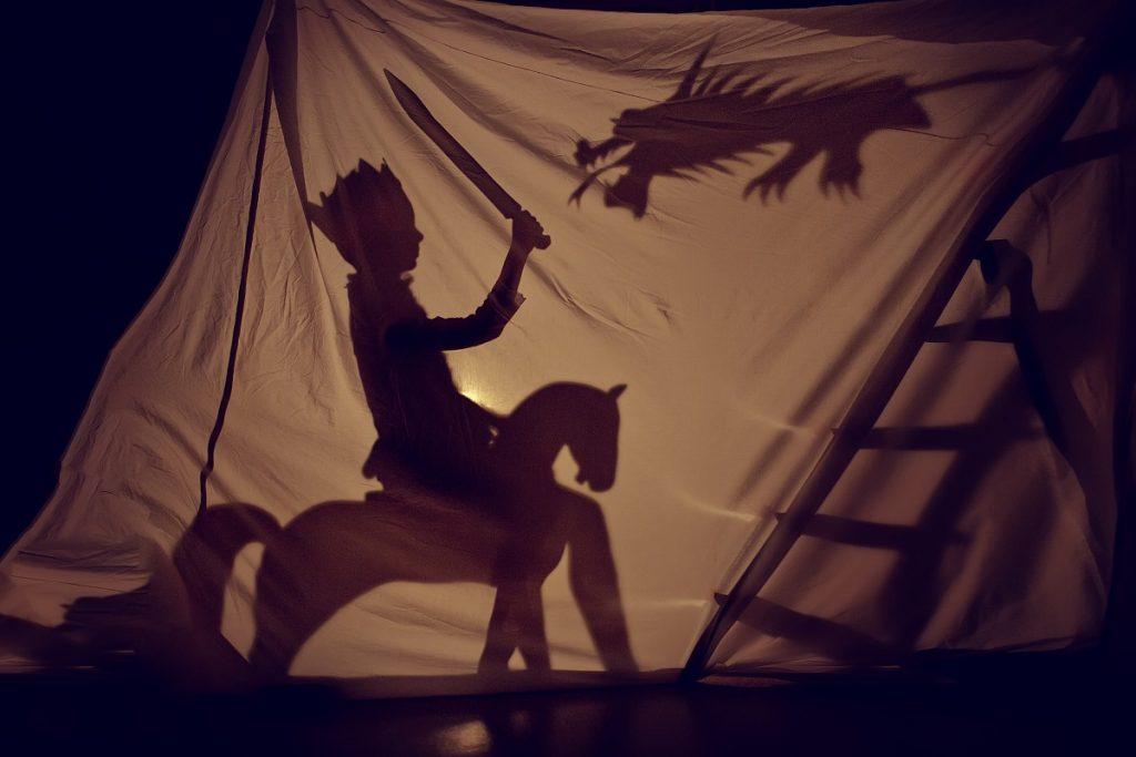 O piesă de teatru în umbră unde se poate observa un copil călare pe un cal în timp ce se luptă cu un dragpn în spatele unui așternut alb luminat cu o lampă pentru a forma umbre