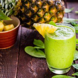 o masă pe care se află un pahar plin cu suc verde care este decorat cu o bucățică de ananas, iar în spate stă un ananas întreg și un bol cu cuburi de ananas