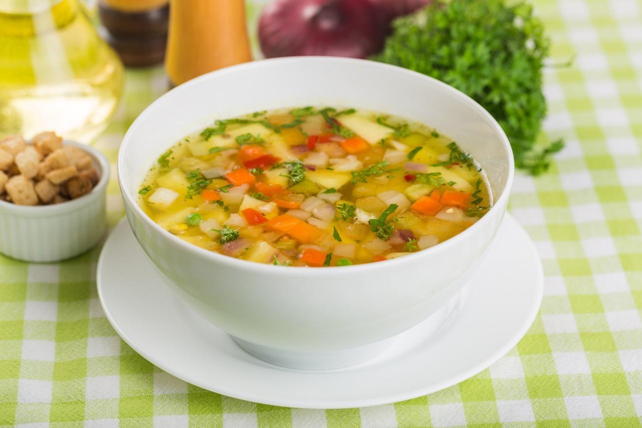 Supă din legume multicolore în bol de servire alb