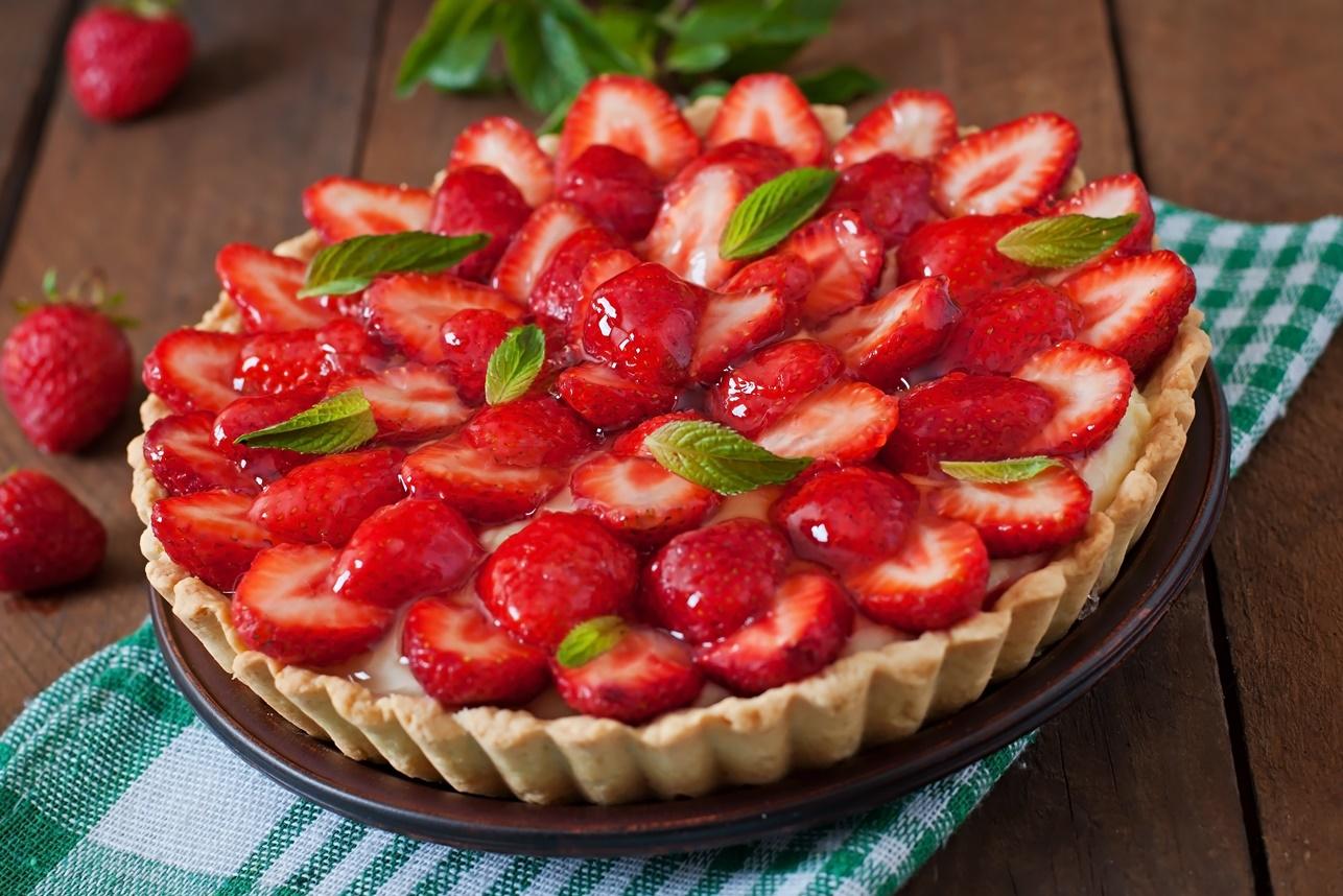 Tartă cu căpșuni și budincă de vanilie pe un platou ceramic de culoare maro
