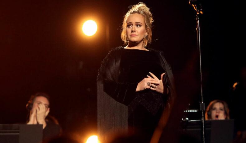Adele, pe scena Premiilor Grammy, în anul 2017, îmbrăcată într-o rochie neagră