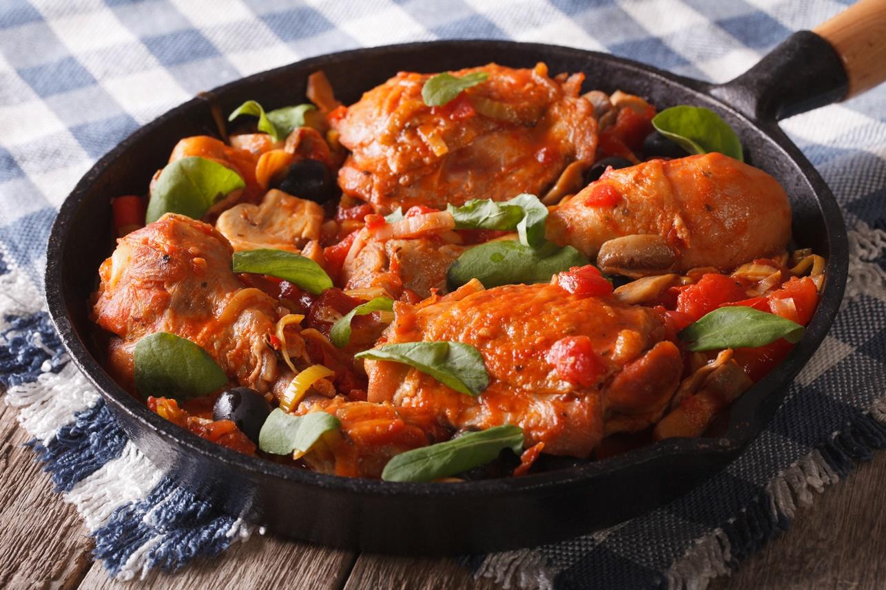 Tigaie cu pulpe de pui picante cu ciuperci și sos de roșii, presărate cu busuioc