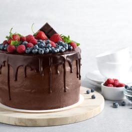 Tort cu cremă de ciocolată, decorat cu fructe, pe un platou de lemn