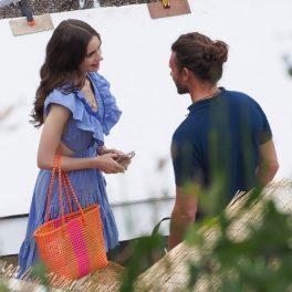 """Un cadru din """"Emily în Paris"""". Protagonista din serial este îmbrăcată într-o rochie albastră, are un coș roșu pe mână. ÎN fața ei este un tânăr cu tricou negru, cu părul strâns la spate."""