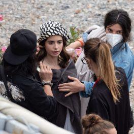 """Un cadru din """"Emily în Paris"""". Echipa de producți se află în pauză. Lily Collins este înfășurată într-un prosop și are o pălărie pe cap."""