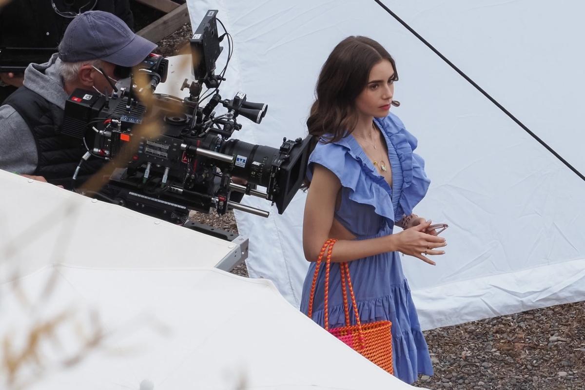 """Un cadru din """"Emily în Paris"""", sezonul 2. Lily Collins poartă o rochie albastră și în spate are un cameraman care filmează."""
