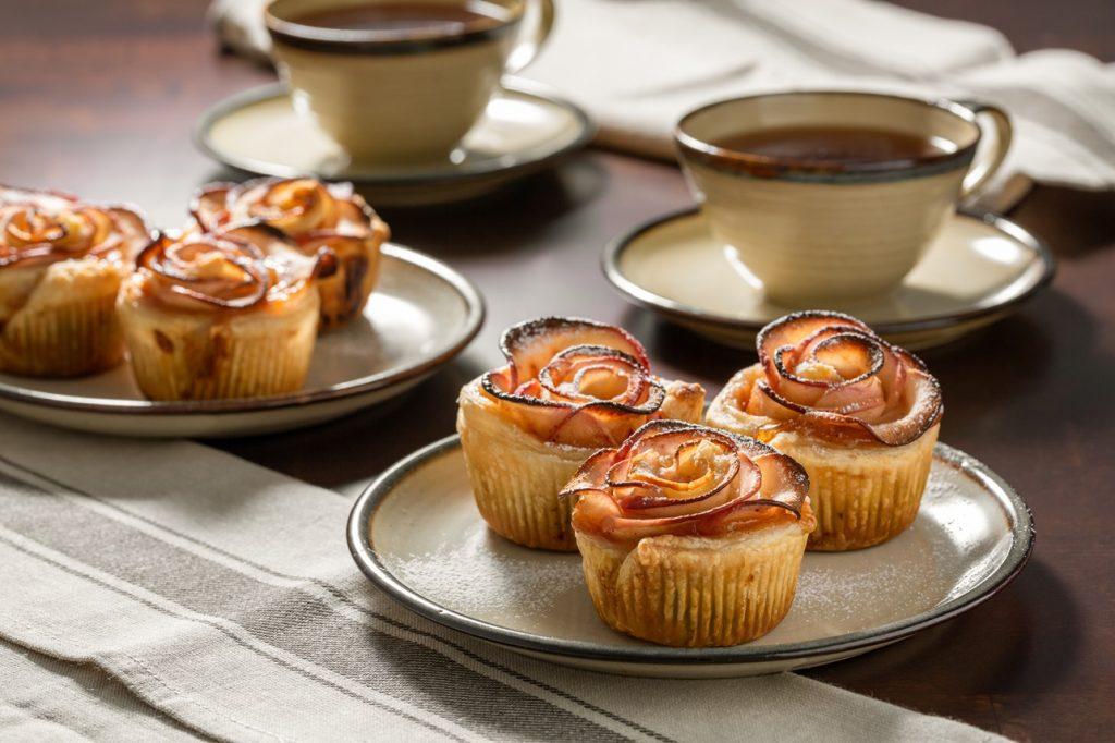 Trandafiri din mere cu aluat foietaj așezați pe farfurii, alături de două cești cu cafea