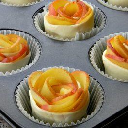 Trandafiri comestibili din mere cu foietaj. înainte de coacere, în forme de brioșe