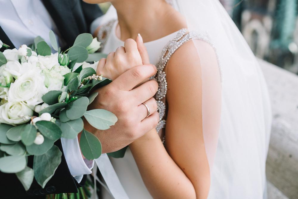 O mireasă, ținută în brațe de soțul ei, cu verighetele la vedere