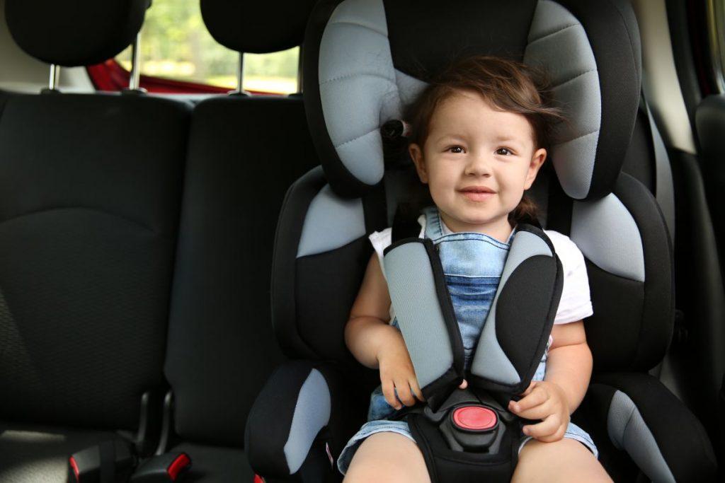 Un băiețel, zâmbește, în timp ce stă într-un scaun auto pentru copii