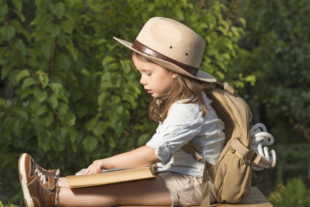 O fetiță îmbrăcată pentru o călătorie cu pălărie, rucsac de munte și pantofi speciali în timp ce stă jos și citește dintr-o carte pentru a răspunde la întrebările vânătoarei de comori, una din cele cinci activități creative de 1 iunie