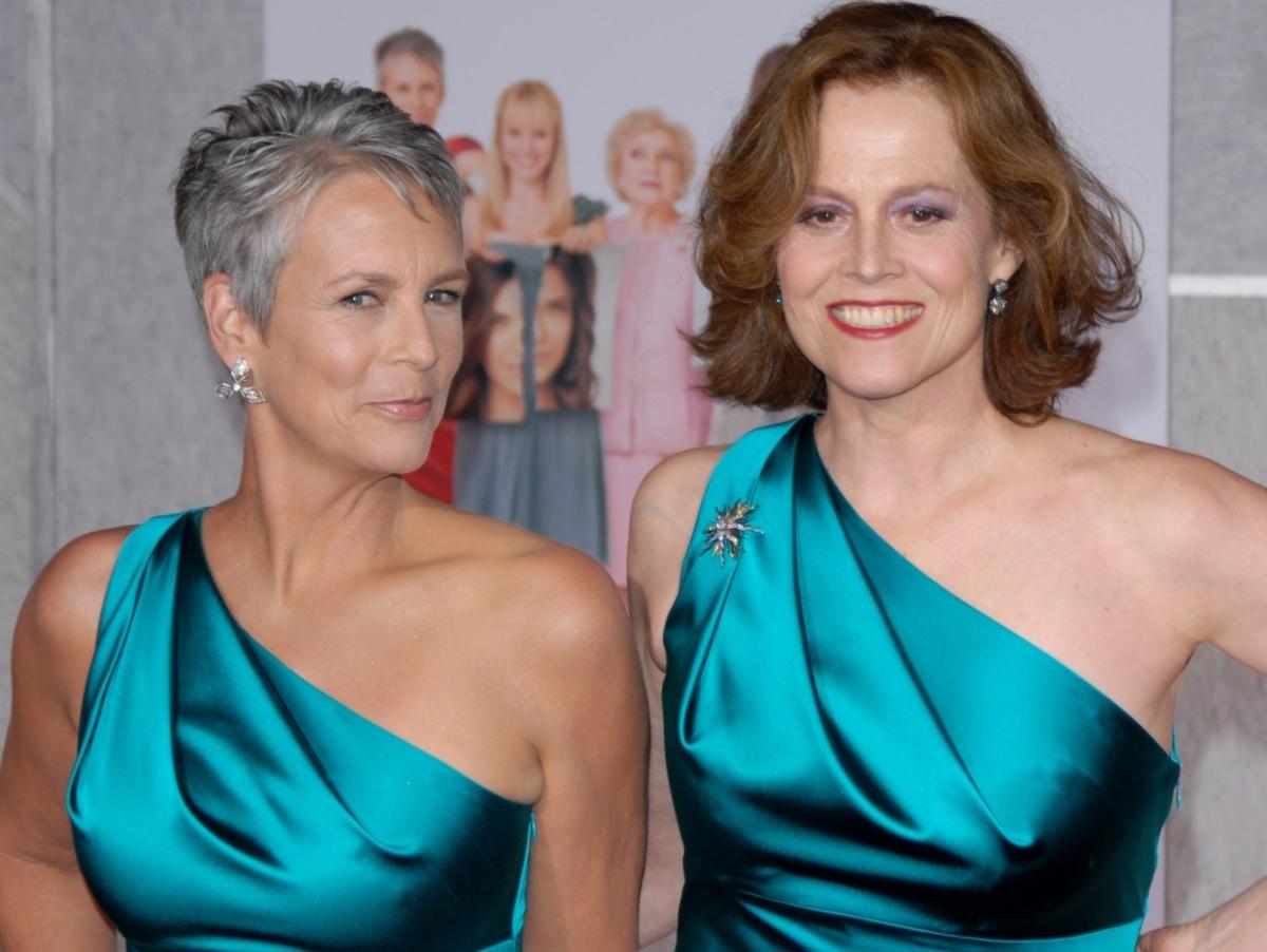 Jamie Lee Curtis și Sigourney Weaver, poartă aceeași rochie de culoare verde, cu umărul gol. Sunt coafate și machiate discret ambele