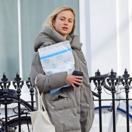 Lady Amelia Spencer îmbrăcată într-o geacă groasă de iarnă gri în timp ce ține în mână un portofoliu în timp ce se plimba în Londra