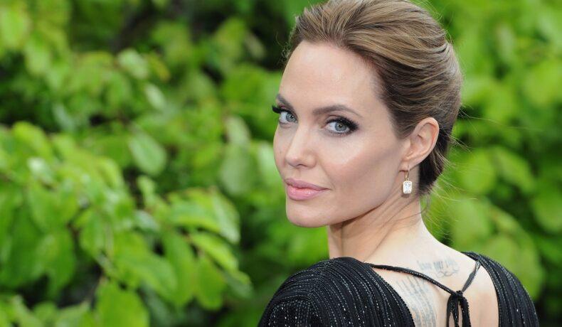 Portret cu Angelina Jolie în timp ce stă cu spatele la cameră și întoarce capul zâmbind la o recepție privată susținută de Disney la Palatul Kensington în mai 2014