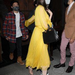 Angelina Jolie într-o rochie galbenă în timp ce îl ține de mână pe fiul său Pax Thien Jolie-Pitt și pleacă de la restaurantul din Los Angeles