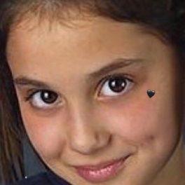 Portreat al Arianei Grande în timp ce zâmbește și are o inimioară neagră pe obraz din adolescență